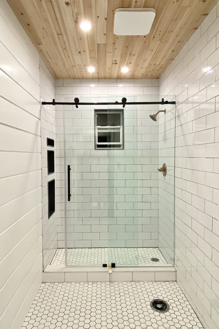 Bathroom renovation with sliding glass door, cedar wood ceiling, and white subway tiles.